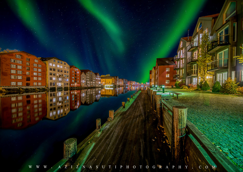 Amazing aurora over Trondheim Brygga and Nidelva river. Here you can see one over the beautiful wooden houses of Trondheim. please note that  some of the green lights come from sidewalk lamps on the ground :).This picture has been  Please feel free to find me by: |Website| ,