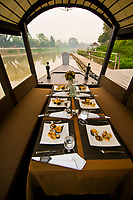 Scorpion river boat with table set for cocktail cruise on the Mae Ping River, Ratilanna Riverside Spa Hotel, Chiang Mai, Northern Thailand