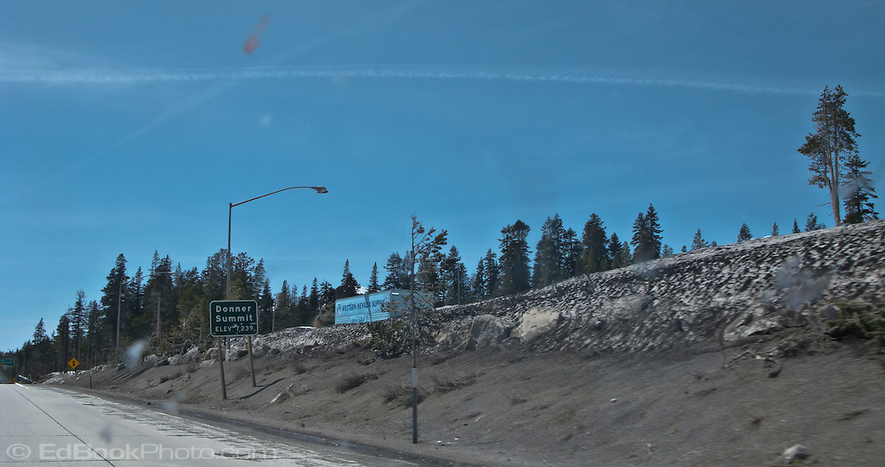 Donner Summit elev 7239 sign on I-80 with bugs on the windshield, snow on the sides of the highway, and jet contrails in the sky