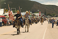 Ladies on donkeys (Equus asinus) lead the Montana Mule Days parade in Drummond Montana, <br /> MODEL RELEASED ON TWO WOMEN IN FRONT ONLY