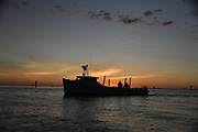 Silhouetted workboat at sunrise