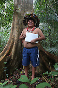 Chief Almir Narayamogo with his apple air computer in the Surui territory, primary rainforest interior.<br /><br />An Amazonian tribal chief Almir Narayamogo, leader of 1350 Surui Indians in Rondônia, near Cacaol, Brazil, with a $100,000 bounty on his head, is fighting for the survival of his people and their forest, and using the world's modern hi-tech tools; computers, smartphones, Google Earth and digital forestry surveillance. So far their fight has been very effective, leading to a most promising and novel result. In 2013, Almir Narayamogo, led his people to be the first and unique indigenous tribe in the world to manage their own REDD+ carbon project and sell carbon credits to the industrial world. By marketing the CO2 capacity of 250 000 hectares of their virgin forest, the forty year old Surui, has ensured the preservation, as well as a future of his community. <br /><br />In 2009, the four clans and 25 Surui villages voted in favour of a total moratorium on logging and the carbon credits project. <br /><br />They still face deforestation problems, such as illegal logging, and gold mining which causes pollution of their river systems