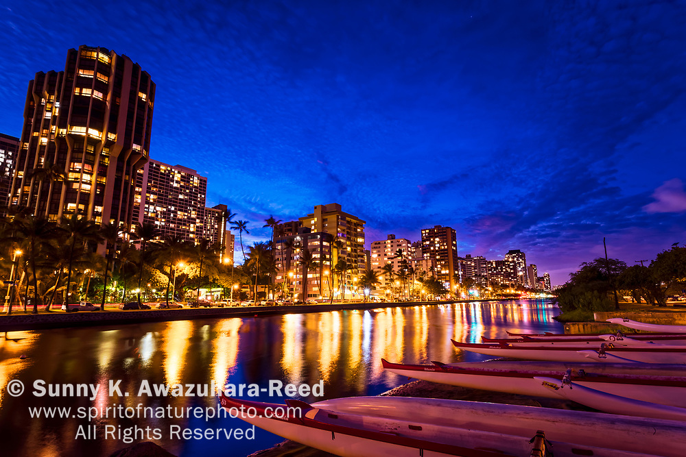 Night scene at Ala Wai Canal and highrise buildings. Outrigger canoes lined up along the shore. Honolulu, Oahu Island, Hawaii.