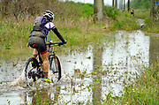 A mountain biker crosses a big puddle during the Fakawi Gravel Grinder 2019