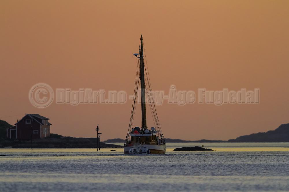 Old boat in the sea summers night, passing by Flåvær, Norway   Gammel båt som passerer Flåvær en sommernatt