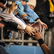 Carolina Panthers quarterback Cam Newton gives the ball to a fan during a game in Charlotte, N.C. ©Travis Bell Photography