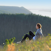 Girl sitting on top of Strelnaya mountain, the highest point on Zhiguli mountains. Girl relaxed and looking to the mountains with green trees. Volga river on background