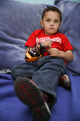 Portrait of a young boy lying down; playing with a toy fork lift truck,