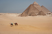 The Pyramids of Giza in Egypt, Menkaure (left),  Kafre (center) and Khufu (Cheops in Greek) on right, with a couple of tourists riding camels.