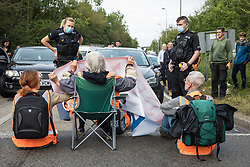 Godstone, UK. 13th September, 2021. A police officer asks climate activists from Insulate Britain to move out of a slip road from the M25, causing long tailbacks on the motorway, as part of a new campaign intended to push the UK government to make significant legislative change to start lowering emissions. The activists, who wrote to Prime Minister Boris Johnson on 13th August, are demanding that the government immediately promises both to fully fund and ensure the insulation of all social housing in Britain by 2025 and to produce within four months a legally binding national plan to fully fund and ensure the full low-energy and low-carbon whole-house retrofit, with no externalised costs, of all homes in Britain by 2030 as part of a just transition to full decarbonisation of all parts of society and the economy.