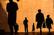 We see six office workers silhouetted against the large orange wall of the Credit Lyonnais Bank. They rush to work while one figure stands and talks into his mobile phone, at Broadgate in the City of London, UK. Several figures who are also reduced to black shapes and without detail that may identify them or their clothes, are hurrying in different directions, carrying a bag or briefcase but the feeling of rushing business is seen and their scale is ambiguous becase we don't know how close or far away they are from each other. This is due to telephoto lens forshortening. Some therefore look giants and some appear tiny. Broadgate Estate is a large, 32 acre (129,000 m²) office and retail estate in the City of London, owned by British Land and managed by Broadgate Estates. It was originally built by Rosehaugh and was the largest office development in London until the arrival of Canary Wharf in the early 1990s.