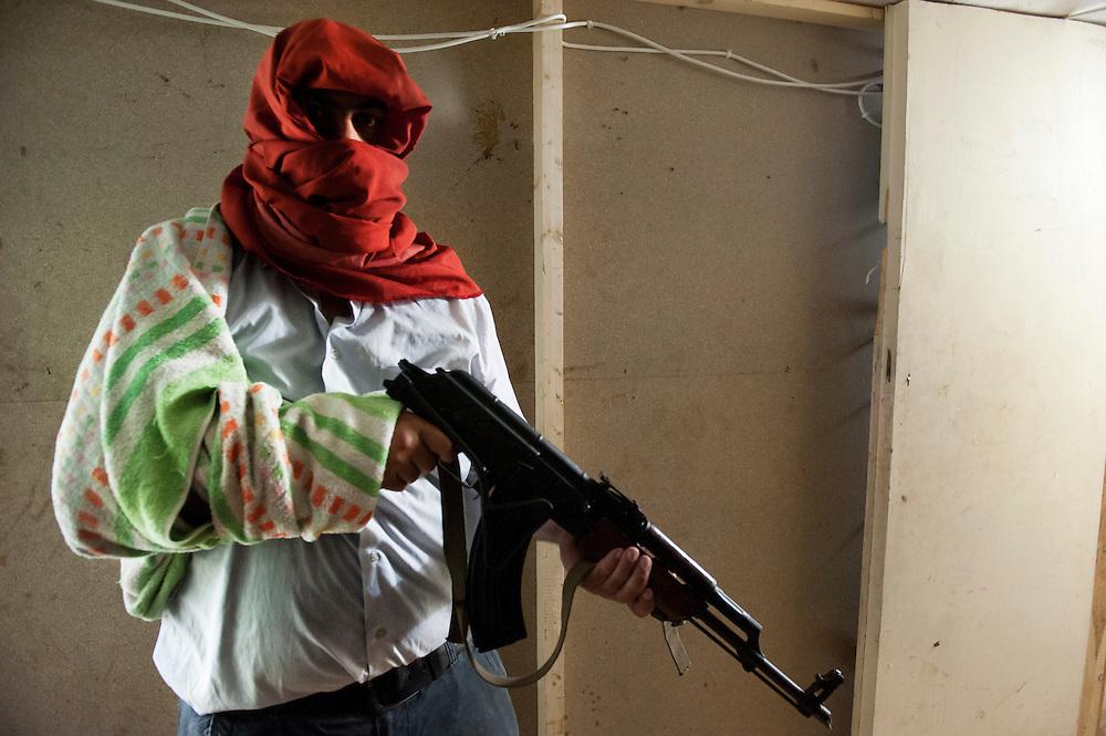 Sunni fighter with a Kalashnikov in the backroom of a shop, this fighter is also a falafel vendor. Sunni neighborhood Bab al-Tebbaneh, Tripoli, Lebanon...Un combattant sunnite avec un kalachnikov neuve dans son arrière boutique, ce combattant est par ailleurs vendeur de fallafel. Quartier sunnite Bab al-Tebbaneh, Tripoli, Liban.