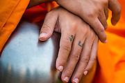 20 OCTOBER 2012 - BANGKOK, THAILAND: A monk with tattoo on his fingers cradles his alms bowl during an alms giving ceremony in Bangkok. More than 2,600 Buddhist Monks from across Bangkok and thousands of devout Thai Buddhists attended the mass alms giving ceremony in Benjasiri Park in Bangkok Saturday morning. The ceremony was to raise food and cash donations for Buddhist temples in Thailand's violence plagued southern provinces. Because of an ongoing long running insurgency by Muslim separatists many Buddhist monks in Pattani, Narathiwat and Yala, Thailand's three Muslim majority provinces, can't leave their temples without military escorts. Monks have been targeted by Muslim extremists because, in the view of the extremists, they represent the Thai state.        PHOTO BY JACK KURTZ