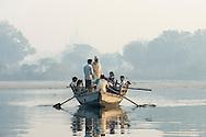 A boat full of passengers crosses the Yamuna river, Mathura, India.