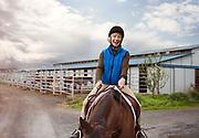 A mature women riding a horse.