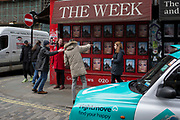 A passer-by offers directions to a couple on the street corner of Berwick and Broadwick Streets on 5th March 2019, in London, England.