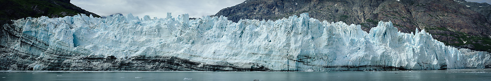 The face of Margerie Glacier, one of the seven tidewater glaciers in Glacier Bay National Park and Reserve in southeast Alaska, is riddled with cracks and crevices. The Margerie Glacier is located on the Tarr Inlet next to another tidewater glacier, Grand Pacific Glacier. Margerie Glacier's one mile wide face has a total height of 350 feet, out of which 250 feet is above the water level and 100 feet is beneath the water surface. For comparison purposes the Statue of Liberty is 307 feet tall. The length of the glacier (2011) is approximately 21 miles. SPECIAL NOTE: This image is a panorama composite consisting of multiple overlapping images stitched together.