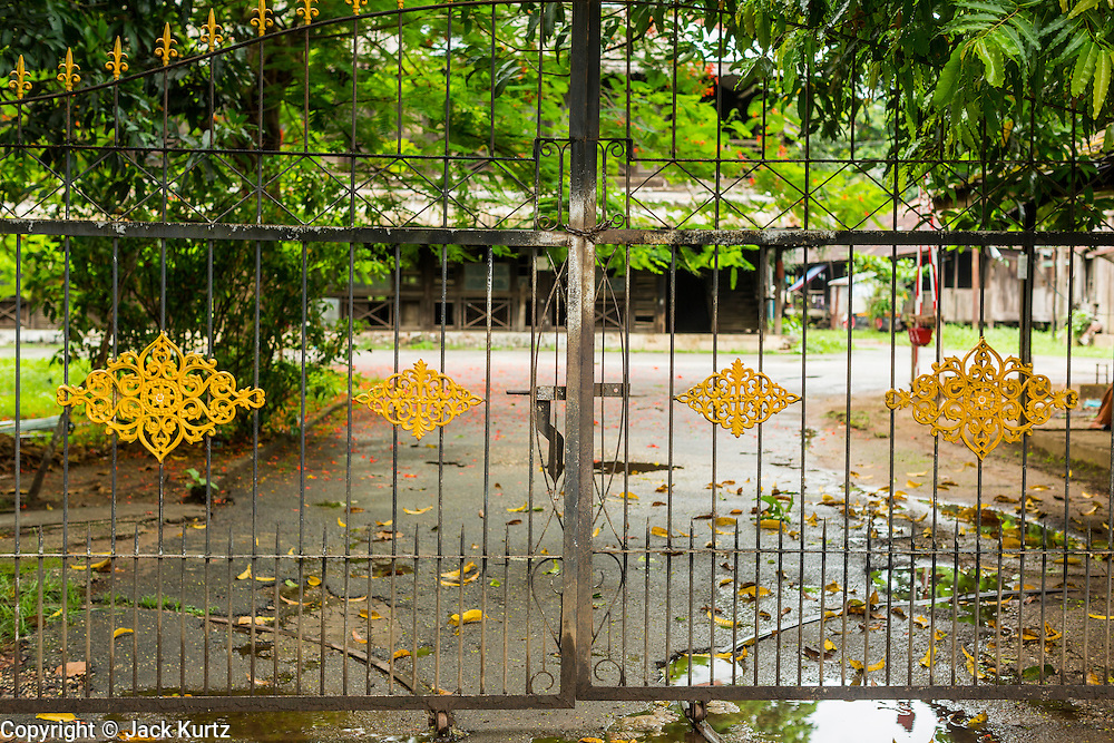 07 JUNE 2014 - YANGON, MYANMAR: The gates to the Pegu Club. The Pegu Club in Yangon was the Officers' Club for the British Army when Myanmar was the British colony of Burma. The club, principally made of teak, is now abandoned and in decay. Squaters have moved into the parts of the complex still standing. Yangon has the highest concentration of colonial style buildings still standing in Asia. Efforts are being made to preserve the buildings but many are in poor condition and not salvageable.    PHOTO BY JACK KURTZ