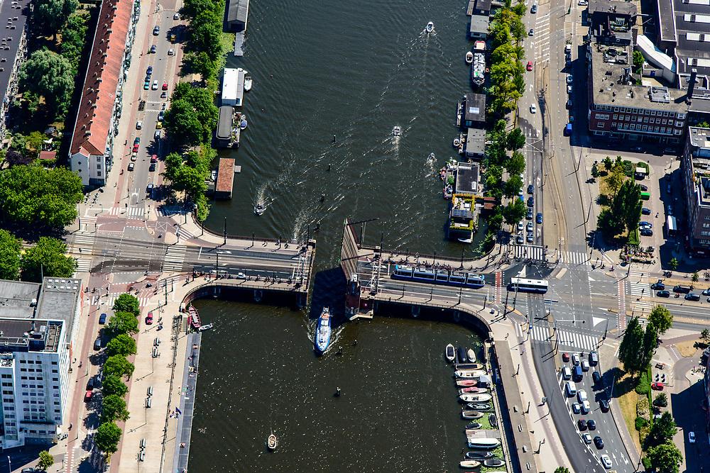 Nederland, Noord-Holland, Amsterdam, 29-06-2018; Amstel met Berlagebrug, omgeving Amstelstation en Omval. Amsteldijk, Weesperzijde. Voor de geopende brug wacht het verkeer, waaronder een tram.<br /> River Amstel near Amstelstation.<br /> <br /> luchtfoto (toeslag op standard tarieven);<br /> aerial photo (additional fee required);<br /> copyright foto/photo Siebe Swart