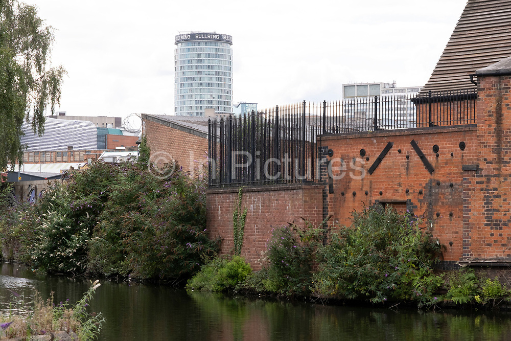 Scene at the end of the Grand Union Canal, on the Digbeth Branch Canal  very close to the city centre where old, crumbling buildings provide a foreground to a modern city and the iconic Rotunda building on 3rd August 2020 in Birmingham, United Kingdom. Birmingham has around 35 miles of canals, said to be more than in Venice, and are very much a reminder of a Birminghams industrial heritage. During the Industrial Revolution these canals were busy, transporting heavy goods like coal, iron, while playing a pivotal role in the development of Birmingham as an industrial powerhouse.
