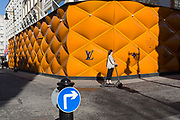 A lady on an electric scooter passes the temporary renovation hoarding of luxury brand Louis Vuitton in New Bond Street, on 25th February 2019, in London, England.
