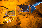 """03 APRIL 2012 - HA LONG, VIETNAM:  Tourists walks through Hang Sung Sot Cave, also called the """"Grotto Of Surprises,"""" the best explored cave in Ha Long Bay. In 1994 UNESCO declared 174 square miles of Ha Long Bay a World Heritage Site. There are nearly 2000 distinct rock islands in the bay, which for centuries has been the home to isolated fishing villages. Now thousands of tourists stream through the bay and around the islands every day on cruise ships. On the Vietnamese mainland, around the town of Ha Long, real estate companies are developing exclusive condominium and apartment complexes for use as weekend homes for people in Hanoi, about a 3.5 hour drive from Ha Long.    PHOTO BY JACK KURTZ"""