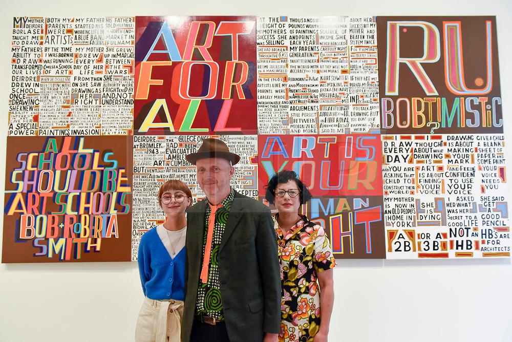 """© Licensed to London News Pictures. 04/09/2018. LONDON, UK.  Celebrated artist Bob and Roberta Smith RA (C), poses with his daughter Etta Voorsanger (L) and wife Etta Voorsanger (R) at the unveiling  of his new work """"The Secret of a Good Life"""", the first display by a Royal Academician in the new Ronald and Rita McAulay Gallery, a new space dedicated to site-specific installations by Royal Academicians in the new Royal Academy in Piccadilly.  This and other works are on display 4 September to 3 February 2019.  Photo credit: Stephen Chung/LNP"""