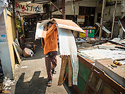 21 SEPTEMBER 2015 - BANGKOK, THAILAND: A demolition worker carries broken down construction materials away from a home being razed near Wat Kalayanamit. Fiftyfour homes around Wat Kalayanamit, a historic Buddhist temple on the Chao Phraya River in the Thonburi section of Bangkok are being razed and the residents evicted to make way for new development at the temple. The abbot of the temple said he was evicting the residents, who have lived on the temple grounds for generations, because their homes are unsafe and because he wants to improve the temple grounds. The evictions are a part of a Bangkok trend, especially along the Chao Phraya River and BTS light rail lines. Low income people are being evicted from their long time homes to make way for urban renewal.    PHOTO BY JACK KURTZ