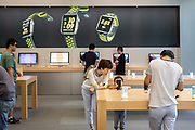 A young customer looks at an Apple Inc. iPhone 7 Plus smartphone at the Apple Store inside the IAPM shopping mall in Shanghai, China, on Friday, Sept. 16, 2016. iPhone sales are slowing in Chinas Apples second largest market, as local upstarts such as Huawei and Xiaomi are eating into the companys high end market.