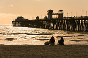 Girls Sitting On The Beach At Sunset By The Oceanside Pier