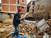 01 MARCH 2017 - KHOKANA, NEPAL: A man scavenges for firewood at the site of a building that was destroyed in the Nepal earthquake of 2015. Wood that can be reused for construction is set aside, but most rural Nepalis cook and heat their homes with firewood, and wood that can't be used in construction is used for firewood. Recovery seems to have barely begun nearly two years after the earthquake of 25 April 2015 that devastated Nepal. In some villages in the Kathmandu valley workers are working by hand to remove ruble and dig out destroyed buildings. About 9,000 people were killed and another 22,000 injured by the earthquake. The epicenter of the earthquake was east of the Gorka district.      PHOTO BY JACK KURTZ