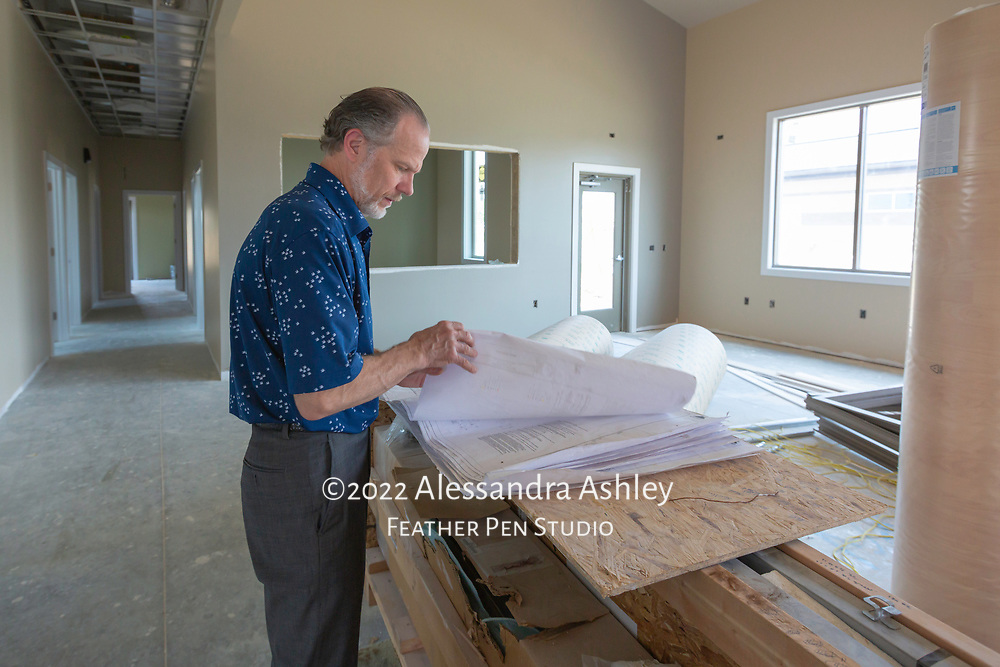 Business owner of Athletic Advantage, Inc., reviews architectural plans onsite at new physical therapy and wellness center building.