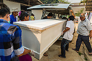 05 MARCH 2014 - MAE SOT, TAK, THAILAND: Workers load the coffin of a deceased patient into a hearse at the Mae Tao Clinic. The Mae Tao Clinic provides  healthcare to over 150,000 displaced Burmese per year and is the leading healthcare provider for Burmese along the Thai-Myanmar border. Reforms in Myanmar have alllowed NGOs to operate in Myanmar, as a result many NGOs are shifting resources to operations to Myanmar, leaving Burmese migrants and refugees in Thailand vulnerable.     PHOTO BY JACK KURTZ