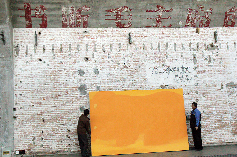Workers hang paintings at Gallery 798 in Beijing. China's art scene is becoming popular among foreign art collectors pushing prices higher.