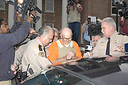 Escorted by Neshoba County Sheriff Larry Meyers,left  and other deputies, accused Klu Klux Klanman and murder Edgar ray Killen center, is lead out  of court in handcuffs and bullet proof vest Wed jan 12,2005 as he is swarmed by the media in Philadelphia Ms. Circuit  court judge Marcus Gordon, ordered a $250,000 bond and set a court date for March 28,2005.(Photo/Suzi Altman)