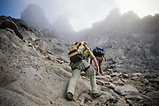 Climbers Brian Polagye and Obadiah Reid scramble up a rock gully on the West Ridge of Mount Stuart, Alpine Lakes Wilderness, Washington.