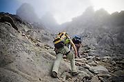 Climbers Brian Polagye and Obadiah Reid scramble up a rock gully on the West Ridge of Mount Stuart, Alpine Lakes Wilderness, Washington.