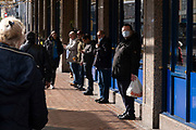 With new local coronavirus lockdown measures now in place and Birmingham currently set at 'Tier 2' or 'high', people wearing face masks wait for buses in the city centre on 14th October 2020 in Birmingham, United Kingdom. This is the first day of the new three tier system in the UK which has levels: 'medium', which includes the rule of six, 'high', which will cover most areas under current restrictions; and 'very high' for those areas with particularly high case numbers. Meanwhile there have been calls by politicians for a 'circuit breaker' complete lockdown to be announced to help the growing spread of the Covid-19 virus.
