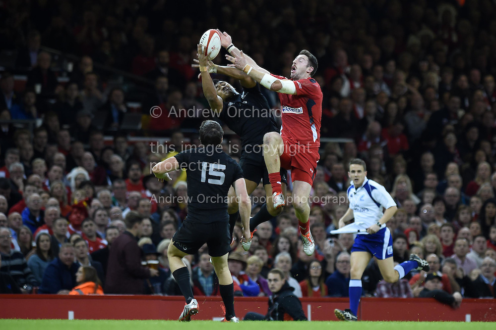 Alex Cuthbert of Wales jumps for a high ball with NZ's Charles Piutau. Dove Men Series 2014, Wales v New Zealand , autumn international rugby match at the Millennium Stadium in Cardiff, South Wales on Saturday 22nd November 2014<br /> pic by Andrew Orchard, Andrew Orchard sports photography.