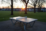 After a weekend of large numbers of Britons leaving London for holiday resorts and coastal beauty spots, and crowding into the capitals parks, the UK government is considering further restrictions of movement in public places to help social distancing during the Coronavirus pandemic. Some public green spaces have been closed by their own local authority but most, such as Ruskin Park in south London, are still open. Warm light from a setting sun shines across a table tennis table in Ruskin Park, on 23rd March 2020, in London, England.