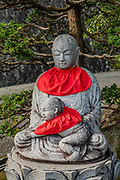 "Buddhist statue of Jizo / Ojizo-sama at Seiganto-ji Temple in Wakayama Prefecture, on the Kii Peninsula, Honshu, Japan. In Japan, Buddhist statues of Jizo (or respectfully Ojizo-sama) can sometimes be seen wearing tiny children's clothing or red bibs, or with toys, placed by grieving parents to protect their lost ones. Ojizo-sama is one of the most loved of Japanese divinities. His features are commonly made more baby-like to resemble the children he protects. His statues are a common sight along roadsides and graveyards. Traditionally, he is seen as the guardian of children, and in particular, children who died before their parents. Jizo has been worshipped as the guardian of the souls of mizuko, the souls of stillborn, miscarried or aborted fetuses (""water children""). Jizo is a Japanese version of Ksitigarbha (Sanskrit for ""Earth Treasury"", ""Earth Store"", ""Earth Matrix"" or ""Earth Womb""), a bodhisattva revered in East Asian Buddhism. Ksitigarbha is usually depicted as a Buddhist monk with a halo around his shaved head. He carries a staff to force open the gates of hell and a wish-fulfilling jewel to light up the darkness.  Seiganto-ji (Temple of the Blue Waves) is a Tendai Buddhist temple. Don't miss the iconic view of thundering Nachi-no-Taki waterfall (133 m, Japan's tallest) paired with Seiganto-ji pagoda. According to a legend, it was founded (near a previous nature worship site) by the priest Ragyo Shonin, a monk from India. Seiganto-ji is part of the Kumano Sanzan shrine complex and is one of the few jingu-ji still in existence after the separation of Shinto and Buddhism forced by the Japanese government during the Meiji restoration. Seiganto-ji is is stop #1 on Kansai Kannon Pilgrimage, and is part of a UNESCO World Heritage Site listed as the ""Sacred Sites and Pilgrimage Routes in the Kii Mountain Range"". Access: by bus from Nachi Station (20 min) or Kii-Katsuura Station (30 min). Ask driver to stop at base of the Daimonzaka trail (""Daimonzaka"" stop); or at"