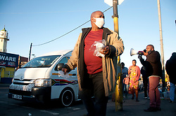 Pastor Poswa handing out masks to commuters at a taxi rank in Mayville.