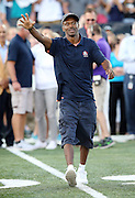 Former Indianapolis Colts wide receiver Marvin Harrison waves while being announced over the public address system as he walks onto the field as a new member of the Pro Football Hall of Fame before the 2016 NFL Pro Football Hall of Fame preseason football game against the Green Bay Packers on Sunday, Aug. 7, 2016 in Canton, Ohio. The game was canceled for player safety reasons due to the condition of the paint on the turf field. (©Paul Anthony Spinelli)