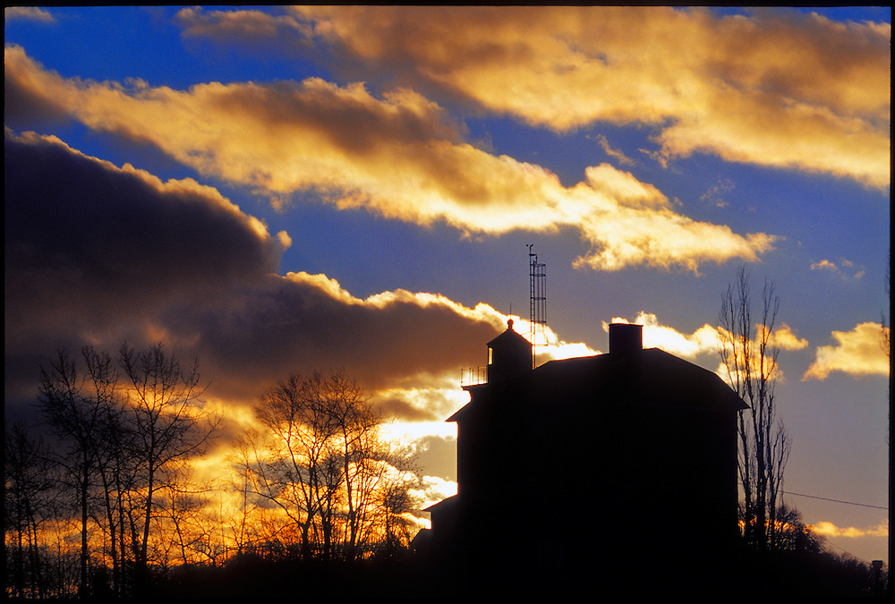 THE MARQUETTE LIGHTHOUSE ON LAKE SUPERIOR IS SILHOUETTED AT DAWN IN MARQUETTE MICHIGAN.