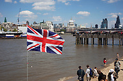 Union Jack flag flies over the River Thames on a bright spring day looking towards St Paul's Cathedral and the City of London. Below the sandy beach is revealed as people enjoy the sand at low tide. London, UK.