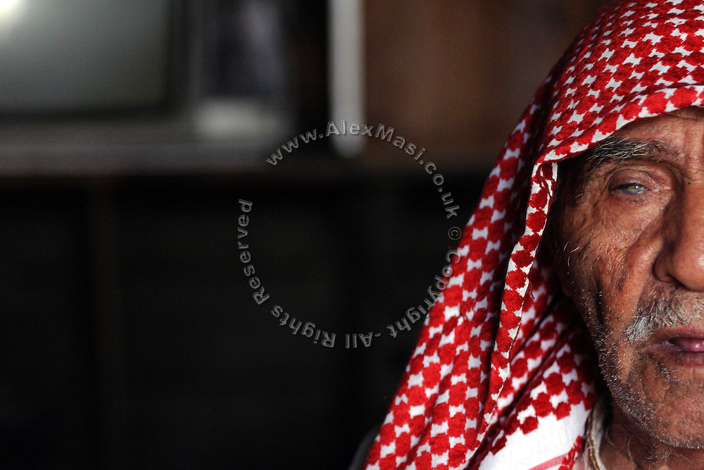 A partially blind Bedouin man is portrayed in the unrecognised village of Wadi el Na'am, pop. 4000, close to Beer Sheva, the capital of the Negev, a large deserted area in the south of Israel. Wadi el Na'am is located near a large industrial site, Ramat Hovav, and has no infrastructure or electric energy. Water is provided only via storage tanks. It has no health services as the only clinic is deemed illegal and bound to be demolished, as the rest of the structures in the area. Numbering around 200.000 in Israel, the Bedouins constitute the native ethnic group of these areas, they farm, grow wheat, olives and live in complete self sufficiency. Many of them were in these lands long before the Israeli State was created and their traditional lifestyle is now threatened by subtle Governmental policies. The seven Bedouin towns already built are all between the 10 more impoverished towns in Israel. .