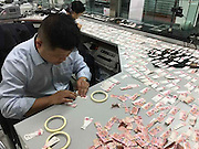 LESHAN, CHINA - OCTOBER 25: (CHINA OUT) <br /> <br /> Psycho Tears Up Over Forty Thousand Savings <br /> <br /> Bank staffs scrape pieces of money together at Rural Credit Cooperative Association of Emeishan City on October 25, 2015 in Leshan, Sichuan Province of China. Over 70-year-old man who is a intermittent psychopath withdrew all savings of 47,600 RMB (about 7,492 USD) and teared up into pieces when his son found. Those pieces of 100-yuan notes were sent to local Rural Credit Cooperative Association and after five-day overtime working of 13 staffs in the night, they were finally clarified clearly according to designs of head portrait and national emblem. Five 100-yuan notes have been split joint and the staffs are tried to work on other, While it\'s not sure how many other 100-yuan notes will be split joint. <br /> ©Exclusivepix Media