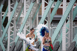 © Licensed to London News Pictures. 29/08/2016. London, UK. Carnival goers in costume pass in front of a painted bridge on Ladbroke Grove on day two of the Notting Hill carnival, the second largest street festival in the world after the Rio Carnival in Brazil, attracting over 1 million people to the streets of West London.  Photo credit: Ben Cawthra/LNP