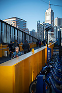 A woman looking at her smartphone crosses the Yarra River on the Sandridge Bridge in the Central Business District of Melbourne, Australia. The pedestrian bridge is a former railway bridge. A bicycle share station is next to the bridge. (August 31, 2017)