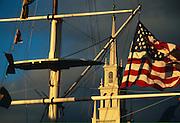 USA, Newport, RI - Nautical/maritime signal flags with the American flag flying fro the Bowen's wharf flag mast frame Newport's Trinity Church..